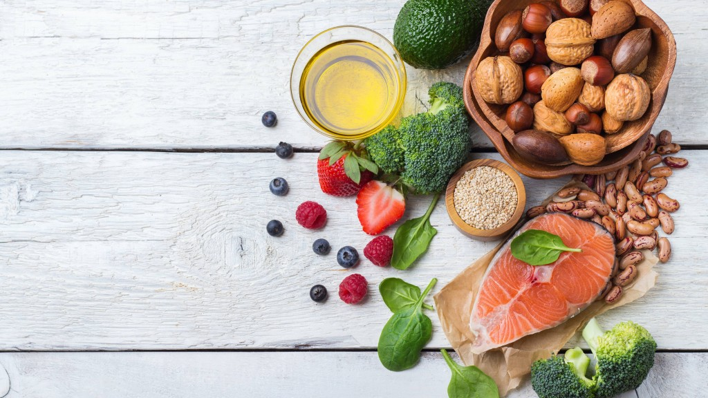 an-assortment-of-foods-included-in-a-diabetes-diet-fruits-and-vegetables-fish-nuts-legumes-whole-grain-on-a-white-wooden-surface-16X9
