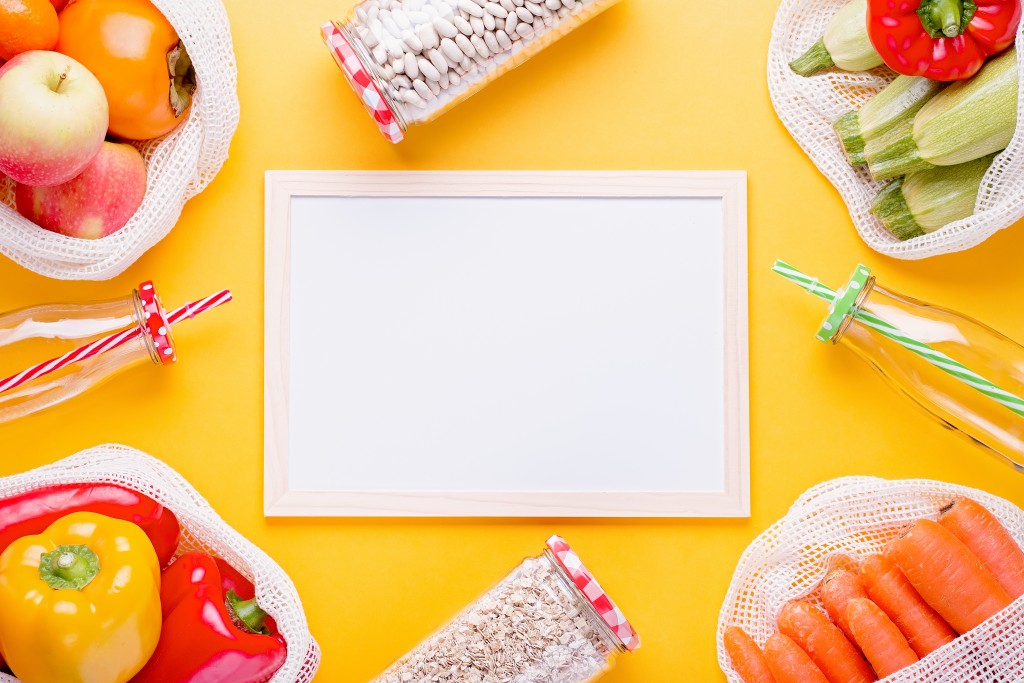 Fresh colorful fruits and vegetables in mesh bags on bright yellow background with white board for text. Zero waste flat lay, copy space. Reusable grocery bags and blank list on yellow