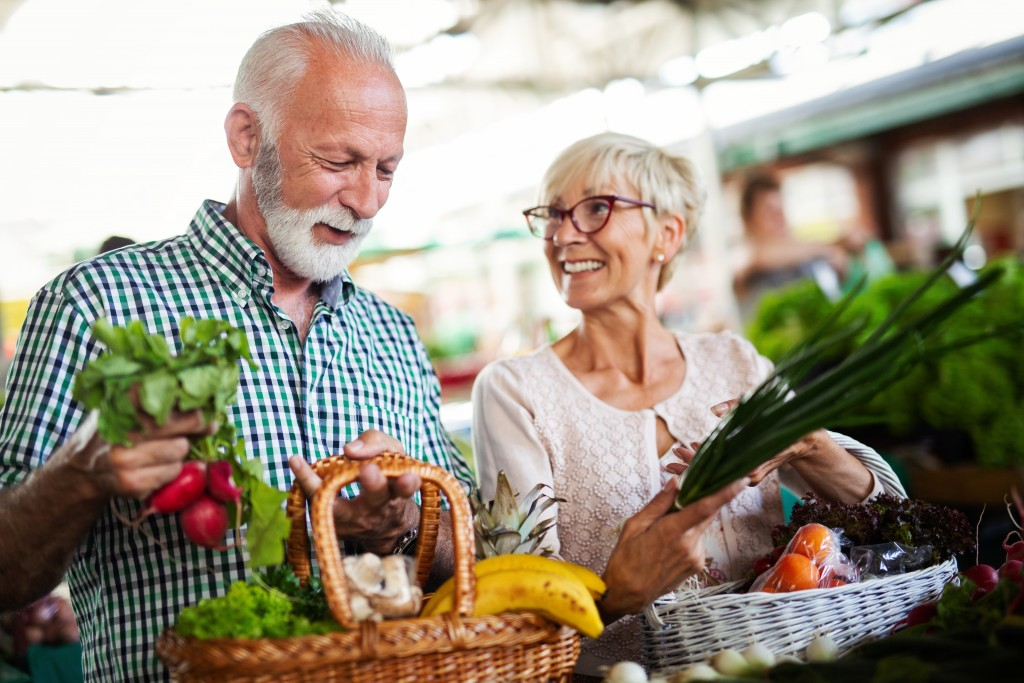 Shopping, food, sale, consumerism and people concept - happy senior couple buying fresh food on the market